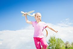 Happy smiling girl holding airplane toy during run Stock Image