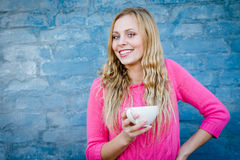Happy smiling girl holding cup of beverage over brick wall. Royalty Free Stock Photo