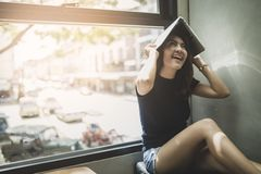 Happy smiling girl holding laptop above head. A Asia happy girl smiling and holding laptop above the head Royalty Free Stock Image