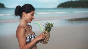 Happy smiling girl holding a pinapple cocktail stock footage