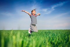Happy smiling girl jumping at the field of wheat Royalty Free Stock Photos