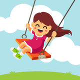 Happy smiling girl kid swinging on a swing Royalty Free Stock Images