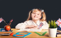 Studying in Classroom. Happy smiling girl learning English language with book before dark background stock photography