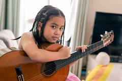 Happy smiling girl learning to play the acoustic guitar Royalty Free Stock Image