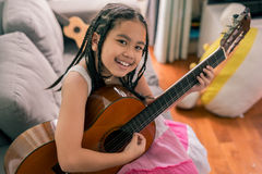 Happy smiling girl learning to play the acoustic guitar Royalty Free Stock Images