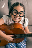 Happy smiling girl learning to play the acoustic guitar Royalty Free Stock Photo