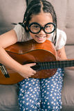Happy smiling girl learning to play the acoustic guitar Stock Photos