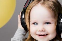 Happy smiling girl listening music in big earphones.