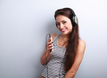 Happy smiling girl listening the music wearing headphones holdin Royalty Free Stock Photos