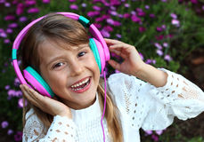 Happy smiling girl with long blond hair, lace clothes listening to music on headphones on a purple blossom flowers background Royalty Free Stock Photos
