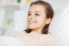 Happy smiling girl lying awake in bed at home Royalty Free Stock Photo