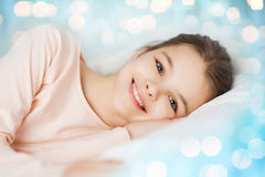 Happy smiling girl lying awake in bed over lights Royalty Free Stock Image
