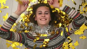 Happy smiling girl lying on the floor, the golden confetti falling on her. After party time. Closeup view. Slow motion. Shot stock video