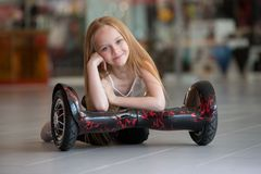Happy and smiling girl with mini segway at trading mall. Teenager riding on hover board or gyroscooter. Royalty Free Stock Image