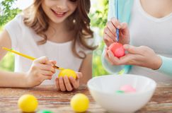 Happy smiling girl and mother coloring easter eggs stock image