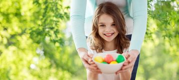 Happy smiling girl and mother with easter eggs stock image