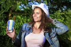 Happy smiling girl in nature with cocktail. Attractive girl in hat and denim jacket on green tree background royalty free stock photography