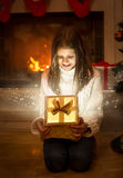 Happy smiling girl opening shiny Christmas gift box. Light and s Stock Photo