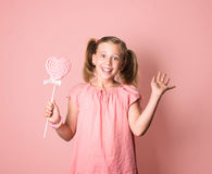 Happy smiling girl in pink dress holding a big heart shaped loll