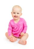 The happy smiling girl in pink dress sits Royalty Free Stock Photos