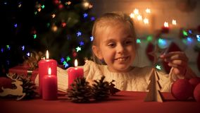 Happy smiling girl playing near sparkling X-mas tree, wooden decor for holiday stock images