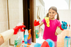 Happy smiling girl polishing mirror at bathroom with cloth Royalty Free Stock Photo