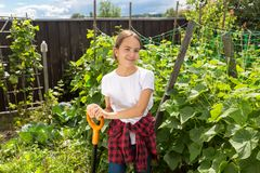 Portrait of happy smiling girl posing in garden with growing vegetables Royalty Free Stock Images