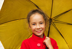 happy smiling girl in a red jacket holding an yellow umbrella Royalty Free Stock Image