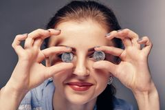 Smiling girl with red lipstick holds golden coins in her hands, closes her eyes. Happy smiling girl with red lipstick holds golden coins in her hands, closes her Royalty Free Stock Photo
