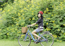 Happy smiling girl riding a bicycle in the park Royalty Free Stock Photography