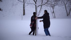 Happy smiling girl running from her boyfriend and hiding behind tree. Young man catches his girlfriend, grabs her and. Both fall in snow. Happy cute couple in stock footage