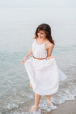 A happy smiling girl in running on the sea shore Royalty Free Stock Photo