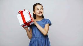 Happy smiling girl shaking gift box stock video