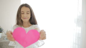 Happy smiling girl showing red heart. Valentine`s Day. Happy smiling girl in a smart dress showing red heart. Valentine`s Day stock footage