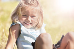 Happy smiling girl sitting in grass Stock Photography