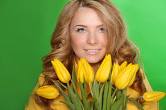 Happy smiling girl with spring-flower yellow tulips isolated on Stock Photography