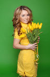 Happy smiling girl with spring-flowering yellow tulips isolated Royalty Free Stock Images