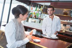 Happy smiling girl standing at bar and flirting with barman. Female Royalty Free Stock Photo