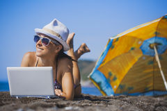 Happy smiling girl is sunbathing with laptop Stock Photo