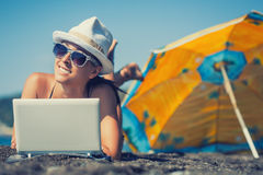Happy smiling girl is sunbathing with laptop Royalty Free Stock Photos
