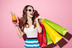 Happy smiling girl in sunglasses drinking cocktail and celebrating purchase Royalty Free Stock Photography