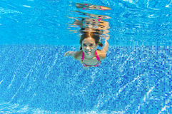 Happy smiling girl swims underwater in blue pool Royalty Free Stock Photography