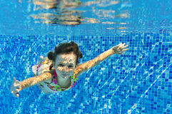Happy smiling girl swims underwater in pool Stock Photo