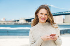 Happy smiling girl texting on a smart phone in the city Royalty Free Stock Image