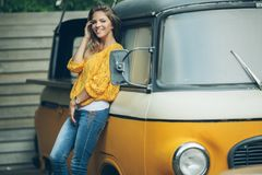 Happy smiling girl is wearing yellow sweater near old retro bus, autumn concept Stock Photo