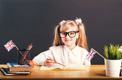 Studying in Classroom. Happy smiling girl wears in smart eyeglasses learning English language with book before dark background stock images