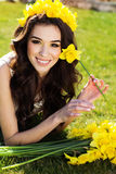 Happy smiling girl with yellow flowers daffodils Royalty Free Stock Photo
