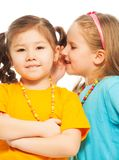 Happy smiling girls. Two little 6-7 years old Asian and Caucasian girls whisper telling secrets mouse to ear, isolated on white Royalty Free Stock Photo