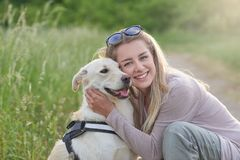 Happy smiling golden dog wearing a walking harness sitting facing its pretty young woman owne royalty free stock photos