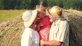 Happy grandparents with little granddaughter in the meadow. Happy smiling grandmother, grandfather and little granddaughter stand near haystack in the meadow at stock video footage